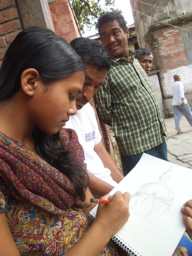 Bipana, imperturbabile, disegna il bianco stupa della piazza di Panga nonostante abbia numerosi osservatori attorno a sè!